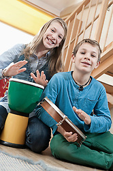 Portrait of two drumming children