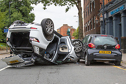 Kensal Green, London August 25th 2015. Four cars were extensively damaged when a Range Rover Sport is said to have overturned after clipping cars waiting at traffic lights on the Harrow Road in North London, just after the intersection of College Road, with the wreckage ending up outside the Mason's Arms pub. Two occupants of the Range Rover were taken to hospital withwhat are said to be minor injuries.