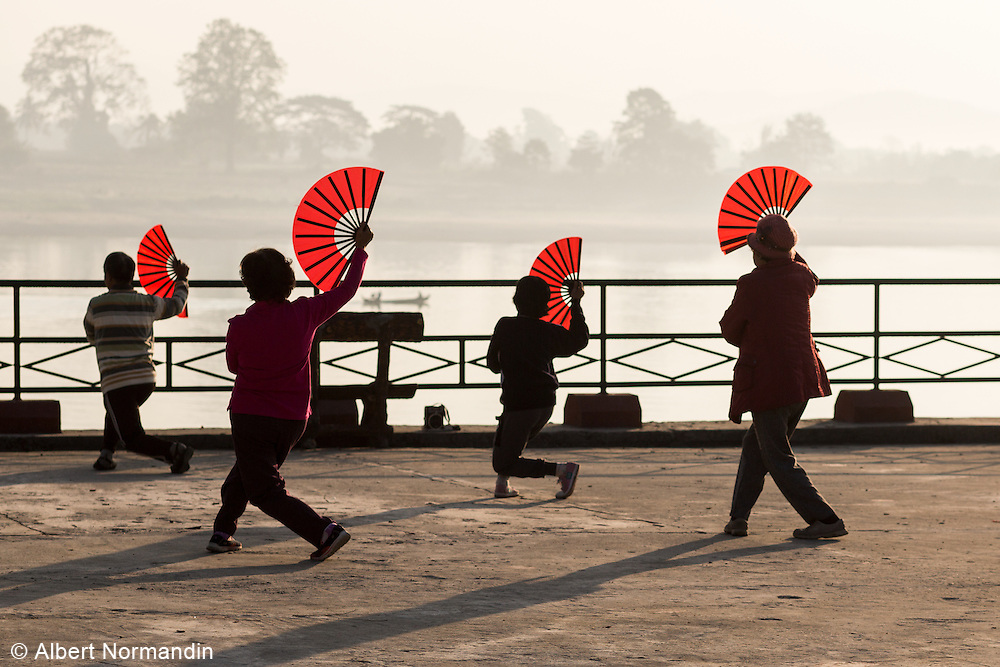 Woman doing traditional morning exercise with fans, Myitkyina