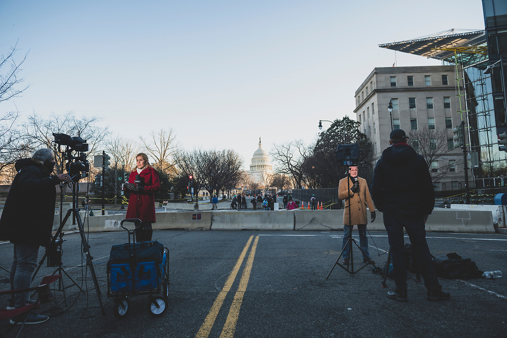 Washington DC, USA - January 19, 2021: Two journalists report live near Capitol Hill on the eve of Joseph Biden's inauguration. On the left, Walkiria Marin reports for MegaTV, a Spanish-language outlet based in the United States. On the right, Björn Soenen reports for VRT NWS based in Belgium.