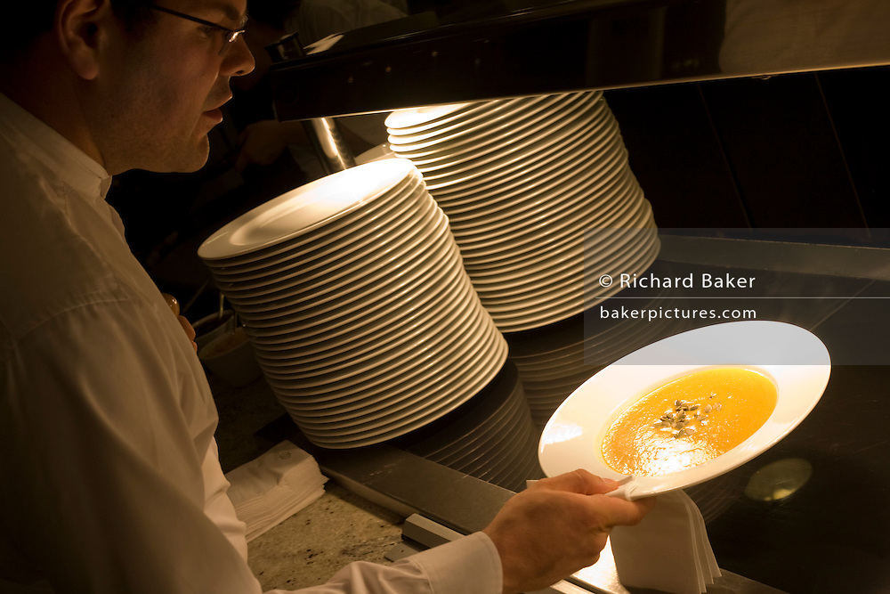 """Using a cloth, a waiter picks up a hot bowl of Butter Squash soup ready for a la carte service in the kitchens at the Vivre restaurant in Sofitel, a 605 bedroom, 27 suite and 45 meeting room accommodation and business hub Heathrow Airport's hub hotel attached to Terminal 5. A stack of clean and unused plates are ready for use on the hot plate that warms them  and we see the waiter leaning over in shadow, carefully taking hold of the bowl so that none of the liquid spills. The man is wearing a smart white shirt and is about to take the dish over to the customer's table. From writer Alain de Botton's book project """"A Week at the Airport: A Heathrow Diary"""" (2009). ."""
