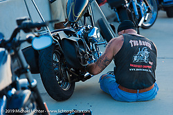 """The Horse Magazine publisher Ralph """"Hammer"""" Janus works on his bike during the ride from Camp Lejeune Marine base in NC to Suck, Bang, Blow in Murrells Inlet in SC on the way to the Smokeout 2015. USA. June 17, 2015.  Photography ©2015 Michael Lichter."""