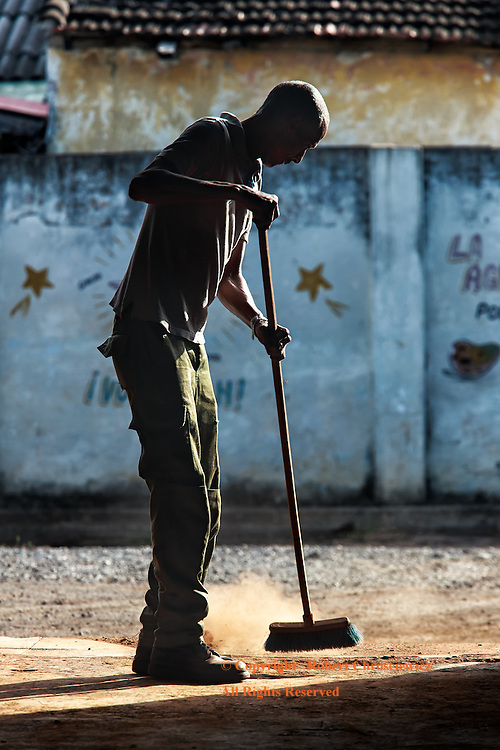 Clean Sweep: In the early morning an elderly man takes the time to sweep out an empty market stall, Cienfuegos Cuba.