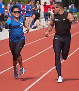 West Point, New York -  Army's Michael Kacer, right, encourages Tatiana Perkins of the Air Force near the finish line of the 200-meters at the 2014 Army Warrior Trials at the United States Military Academy Preparatory School on Tuesday, June 17, 2014.<br />  Hosted by the U.S. Army Warrior Transition Command (WTC), the trials determine which athletes will compete at the 2014 Warrior Games this fall in Colorado Springs, Colorado.