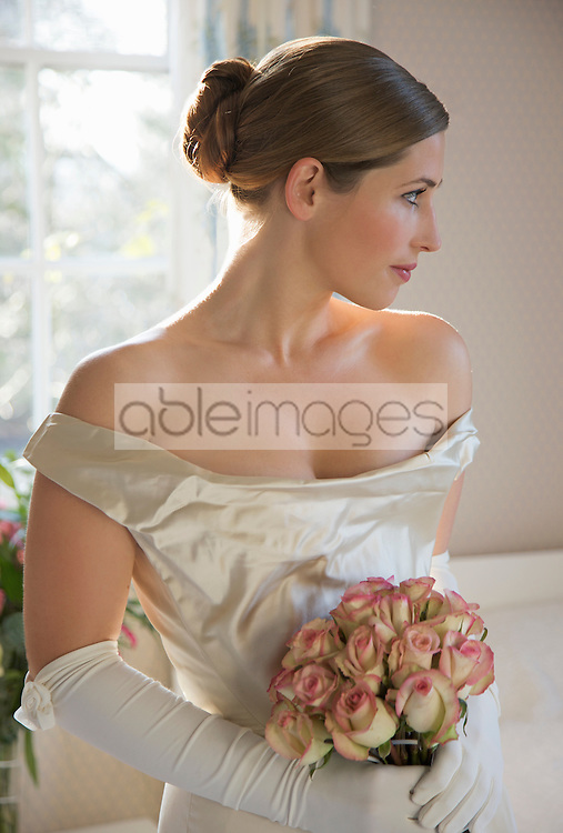 Close up of a bride in a white wedding gown holding a bouquet of roses and looking to one side