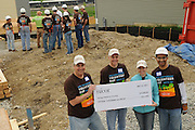While a crew of volunteers gets oriented, Nicor Inc. officials present a check to a Habitat for Humanity home building project in West Chicago, Illinois on Saturday, May 21st, 2011 during Nicor's 15th Volunteer Day. The company's annual event includes volunteering at outdoor clean ups at local social service agencies, food sorting at area pantries and energy-saving improvements at the homes of senior citizens. For additional information, visit nicor.com or contact Richard Caragol at 630-388-2686.