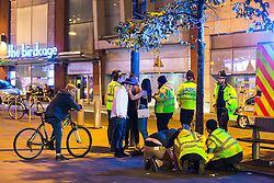 © Licensed to London News Pictures . 11/09/2016 . Manchester , UK . Taxi marshals help a woman , lying collapsed on the pavement on Withy Grove , as an ambulance arrives . Revellers out in Manchester City Centre . Photo credit : Joel Goodman/LNP