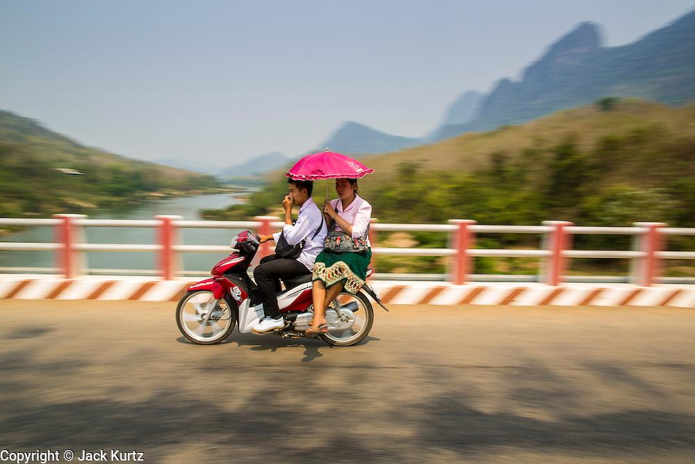 15 MARCH 2013 - BAN SOMSANOUK, LAOS: A couple on a motorcycle cross a bridge over the Nam Ou River in Ban Somsanouk near Luang Prabang, Laos.   PHOTO BY JACK KURTZ