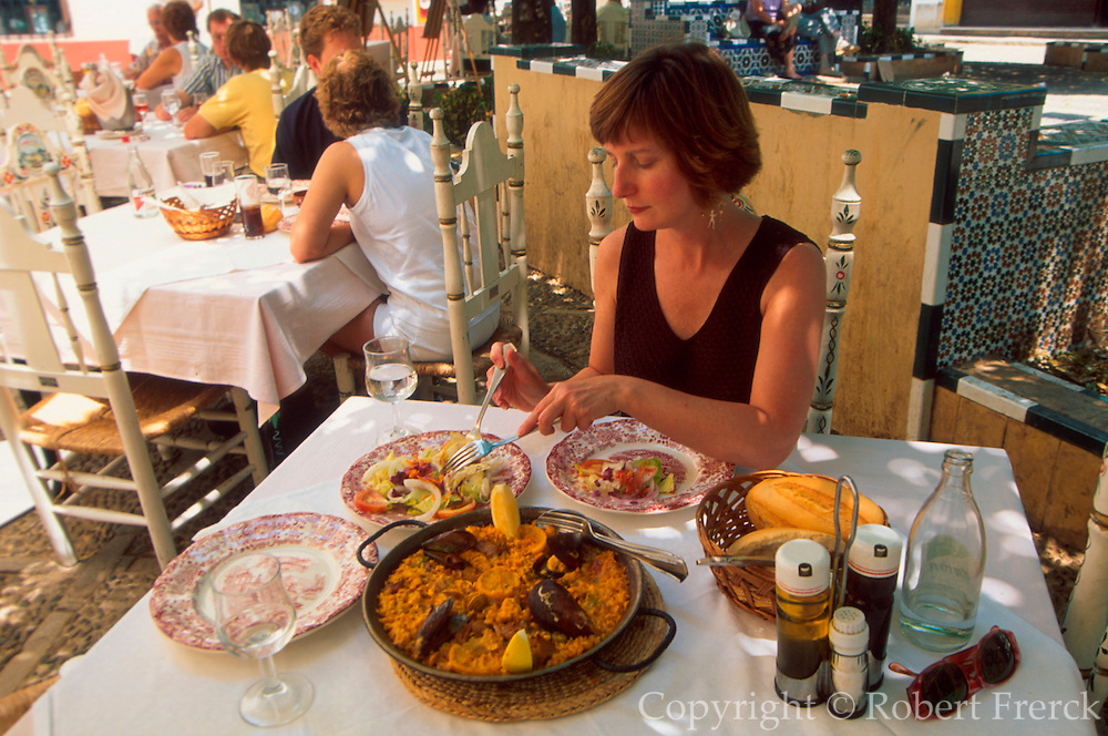 SPAIN, SEVILLE, FOOD outside cafe in the Barrio de Santa Cruz; person eating paella and ensalada mixta, two traditional Spanish dishes