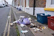 Food waste is spread across the pavement in a seaside side-street, after early morning seagulls ripped open a plastic bag, on 26th July 2021, in Whitstable, Kent, England.