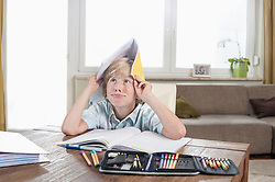 Bored boy with open book on head, Bavaria, Germany