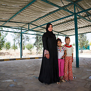 Salsabeel, 30, her three children, and her husband fled Syria. After their home was destroyed, they had nothing left. Salsabeel's children — her two girls and her son Hamza, 3, are everything she has now.<br /> <br /> She and her daughters Bayal and Nada are standing under a community garden cover that was built to help encourage Jordanians and Syrians to socialize with oneanother. Sahal Huron, Jordan, May 2015.