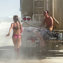 A woman runs behind a water truck to clean off Saturday afternoon, Sept. 1, 2007 during the annual Burning Man Festival on the Black Rock Desert near Gerlach, Nev. ..Photo by David Calvert/Nevada Sagebrush