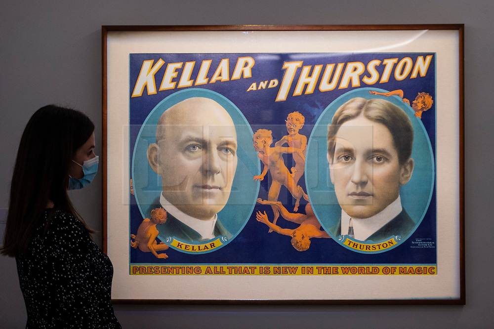 """© Licensed to London News Pictures. 24/09/2021. LONDON, UK. A staff member views a vintage poster of """"Harry Kellar (Kellar) and Howard Thurston"""", printed c.1907, (Est $8,000-12,000). Preview of a collection spanning the history of magic from celebrity magician Ricky Jay.  The works are being shown in Sotheby's, New Bond Street, ahead of their auction in New York on 27 and 28 October.  Photo credit: Stephen Chung/LNP"""