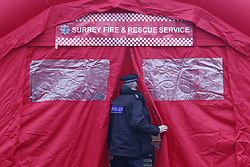 © Licensed to London News Pictures. 02/02/2021. Woking, UK. A police officer enters a Surrey Fire & Rescue tent at Woking fire station ahead of delivery of Covid test kits in the Goldsworth Park area in Surrey, where some cases of the South African variant of Covid-19 have been found. Public health England are carry out surge testing for selected parts of the Goldsworth Park, St Johns and Knaphill areas of Woking. Photo credit: Peter Macdiarmid/LNP