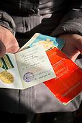 Retired BAM (Baikal-Amur Mainline) volunteer shows her paperwork from her time working on the railway in Baikalskoe Village on Lake Baikal. Siberia, Russia