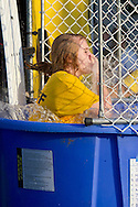 Middletown, New York - A girl holds her nose while falling into the water at a dunking booth during the Camp Funshine Carnival Night on Aug. 16, 2012. The night celebrated the Middletown YMCA summer camp, which ended the next day.