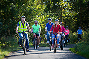 A group of male and female cyclists tour around Staplehurst, Kent, England, UK.  They are riding electric bikes