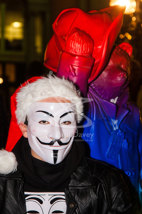 """London, December 23rd 2014. Online activism group Anonymous march through London from the City to the BBC's HQ on Great Portland Street in protest against alleged biases and coverups of a """"paedophile ring"""". PICTURED: Paddington Bear poses with a protester in his Guido Fawkes mask."""