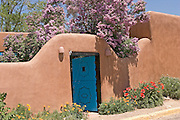 Adobe wall and blue door and flowers in Taos, NM