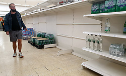 © Licensed to London News Pictures. 30/07/2021. London, UK. A shopper walks past nearly-empty shelves of bottled drink water in Sainsbury's, north London. Record breaking numbers of people have been forced to self-isolate after being alerted by the NHS Covid-19 app. The pingdemic has seen staff shortages at supermarkets, resulting in less stock making its way to supermarket shelves. Labour leader Sir Keir Starmer has demanded that the government brings forward the end to self-isolation from 16 August to 7 August. Photo credit: Dinendra Haria/LNP