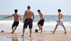 People play football on Bournemouth beach in Dorset as forecasters predict that a wave of warm air will move across the country in the coming days.