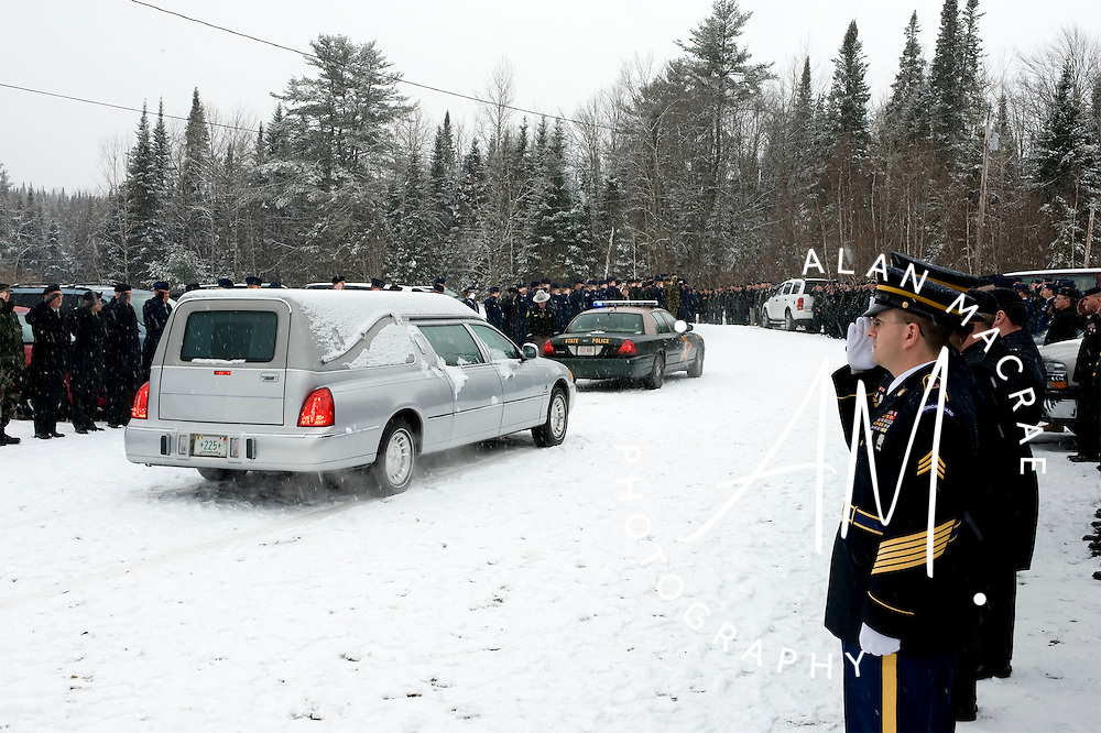 A hearse carrying the casket of NH Army National Guard Sergeant David Stelmart is escorted from the church following Monday's memorial service in Bethlehem.  (Alan MacRae/for the Monitor)