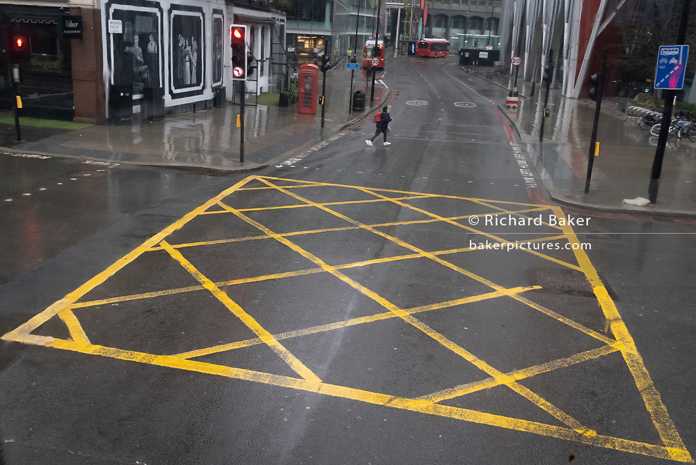 With most Londoners still working at home, a solitary pedestrian dashes out to cross the road where a yellow grid box junction remains empty during the third lockdown of the Coronavirus pandemic, on 22 February 2021, in London, England.
