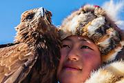 Portrait of young Kazakh eagle huntress with her golden eagle (Aquila chrysaetos), Altai Mountains, Bayan Ulgii, Mongolia