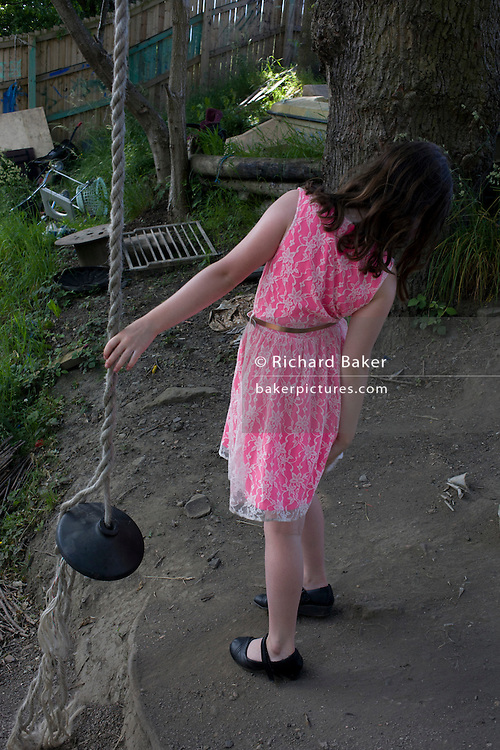 Girl and rope swing in risk averse playground called The Land on Plas Madoc Estate, Ruabon, Wrexham, Wales.