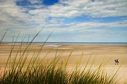 Walkers pass along the vast beach at Burnham Overy Staithe, North Norfolk Coast, England, UK.