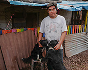 Anyelo Espejo, co-founder and operator of the  Soy Callejerito dog shelter, poses with two of the rescued dogs.