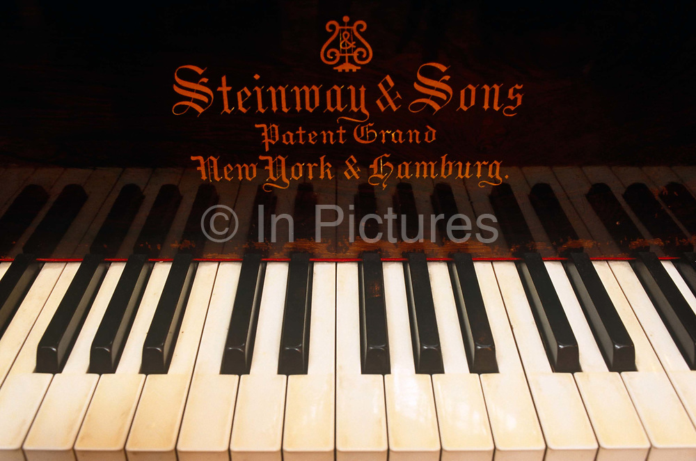 Seen in close-up, we see the keys of a Steinway grand piano. The esteemed manufacturer's logo Steinway & Sons is written above the words Patent Grand and New York & Hamburg. This piano was part of an auction held by Bonhams of the contents of Stokesay House, a Victorian mansion that was locked up for decades but being sold off after the last member of the rich industrialist family of John Derby-Allcroft whose ancestors could no longer afford the property's upkeep. Its contents of almost pristine collection of Victoriana personal effects and furniture, clothing, and memorabilia that was largely stored away from the fading and deteriorating qualities of daylight, went under the hammer and the house is now a hotel. The piano was in almost perfect working order apart from the yellowing ivory keys having been covered under cloth.
