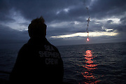 Wietse Van Der Werf watches a solo flare as it drifts over Antarctica's Souther Ocean - Sea Shepherd's single firework celebrating the 2009 New Year as the ship sailed over the International Date Line. (Photo by Adam Lau)