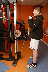 Boy using weights at an inclusive fitness gym,