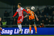 Brentford forward Ollie Watkins (11) and Barnet defender Elliott Johnson (3) challenge in the air during the The FA Cup fourth round match between Barnet and Brentford at The Hive Stadium, London, England on 28 January 2019.