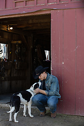 cowboy with his dog by a barn