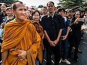 16 DECEMBER 2015 - BANGKOK, THAILAND:   A Buddhist monk waits in the crowd for the funeral procession of Somdet Phra Nyanasamvara, who headed Thailand's order of Buddhist monks for more than two decades and was known as the Supreme Patriarch. The Patriarch died Oct. 24, 2013, at a hospital in Bangkok and was cremated today. He was 100. He was ordained as a Buddhist monk in 1933 and appointed as the Supreme Patriarch in 1989. He was the spiritual advisor to Bhumibol Adulyadej, the King of Thailand when the King served as a monk in 1956. Tens of thousands of people lined the streets during the procession to pray for the Patriarch.   PHOTO BY JACK KURTZ