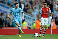 Manchester City's James Milner passing the ball while Arsenal's Mathieu Debuchy looks on. Barclays Premier league match, Arsenal v Manchester city at the Emirates Stadium in London on Saturday 13th Sept 2014.<br /> pic by John Patrick Fletcher, Andrew Orchard sports photography.
