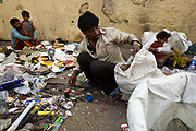 Buddhi-Lala and Roshan sort rubbish into piles to sell on the pavement where they live, Karol Bagh, New Delhi, India.