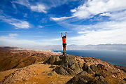 Female hiker celebrates her achievement on reaching the summit of the colourful Eilat mountains