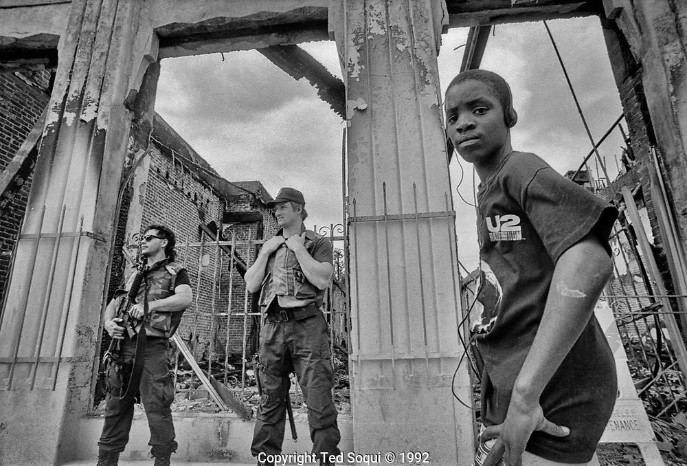 "A kid wearing a U2 ""Rattle and Hum"" t-shirt listens to music on his headphones next two two heavily armed officers in front a building that was burned down during the LA92 riots.<br /> 1925 W. Adams Blvd.<br /> <br /> 25 before and after LA92 photo project."