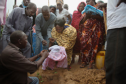 Surrounded by family and close friends, Zendia Eluzai lays to rest her deceased newborn grandchildren in Juba, South Sudan.
