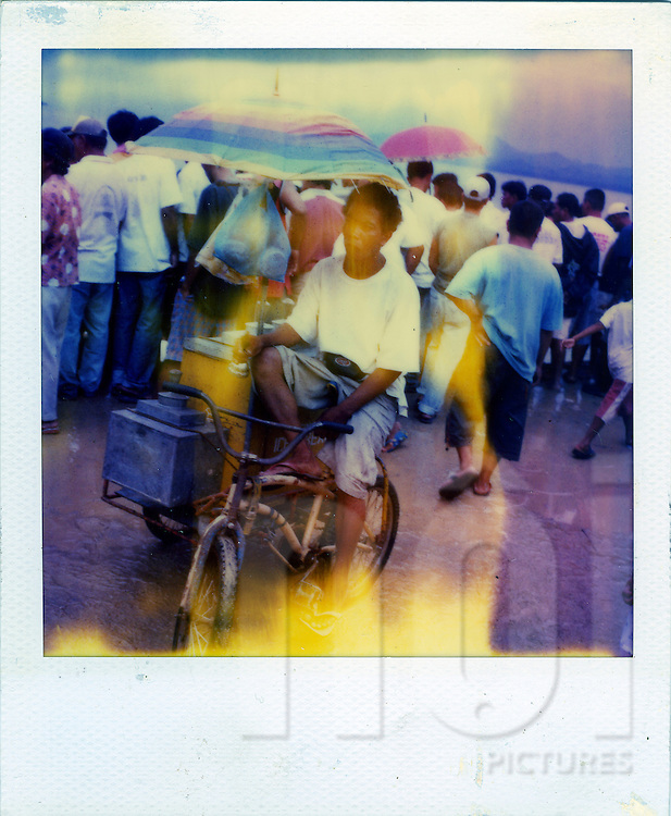 Old Polaroid of a Filipino vendor sitting on a bicycle, beside a crowd on the beach, ringing a bell with his hand to attract attention of the crowd, which is focused in the opposite direction, Palawan Island, Philippines, Southeast Asia