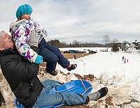 The snow was getting thin but it was still fast and fun as Mark Febbi hoists Ella Febbi up onto his lap for a ride down the sledding hill during Winter Fest at Prescott Farm on Saturday afternoon.  (Karen Bobotas/for the Laconia Daily Sun)