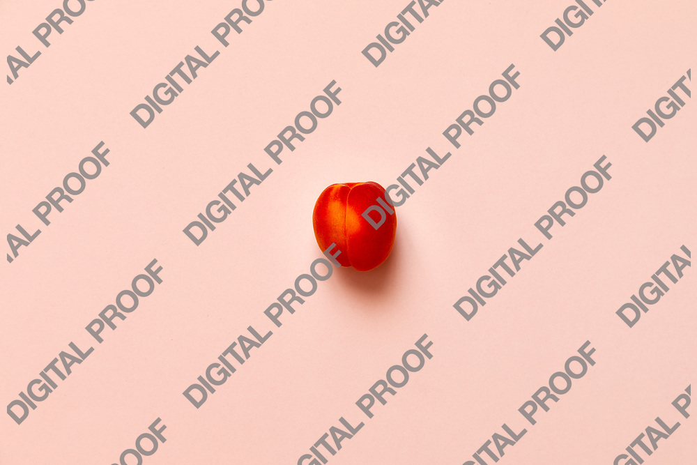 Lonely Apricot  isolated over a pink background viewed from above, flatlay style