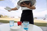 waiter serving coffee at an outdoor restaurant