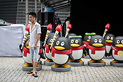 A man stands next to statues of the QQ mascot outside Tencent Holdings Ltd.s current headquarters in Shenzhen, China, on Monday, Aug. 22, 2016. The new headquarters for Tencent, a Chinese internet giant and maker of popular apps such as QQ and WeChat,  is a $599 million project aimed at creating a campus-like atmosphere for the urban setting. Scheduled for completion next year, the Shenzhen skyscraper could become one of the largest labs for new internet services and connected devices.