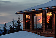 Sunset colors reflect off of cabin windows as Mount Redoubt stand in the distance