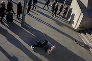 Commuters notice a young skateboarder lies in pain after flying through the air and landing heavily after a acrobatic jump down steps.